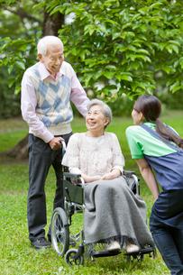車いすに乗ったシニア女性と話す女性介護士とシニア男性の写真素材 [FYI02069343]