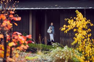 キャリーバッグを持ち廊下を歩くミドル女性の写真素材 [FYI02069360]