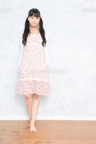 壁際で裸足で立っている若い女性の写真素材 [FYI02069378]