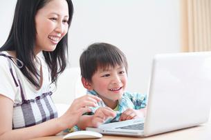楽しそうにパソコンの画面を見ている母と息子の写真素材 [FYI02069383]
