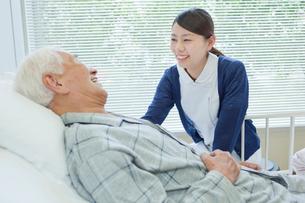 ベッドで横になるシニア男性と笑顔で話す看護師の写真素材 [FYI02069394]