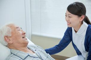ベッドで横になるシニア男性と笑顔で話す看護師の写真素材 [FYI02069403]