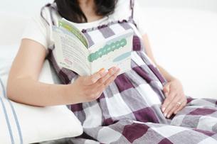 母子手帳を手におなかを優しく触る妊婦の写真素材 [FYI02069419]