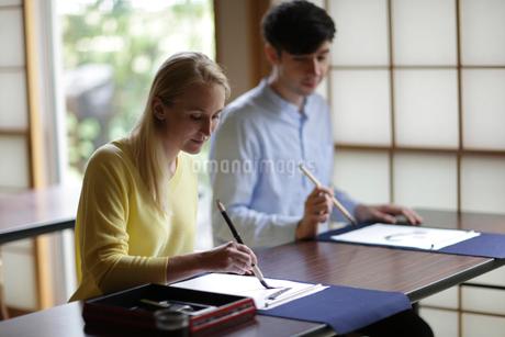 書道をする外国人カップルの写真素材 [FYI02069421]