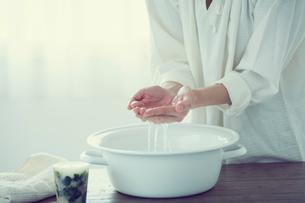 ウォッシュタブの水をすくう女性の手元の写真素材 [FYI02069427]