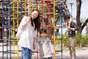 公園のジャングルジムで遊ぶ4人家族の写真素材 [FYI02069434]