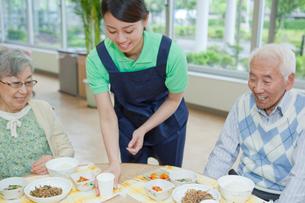介護施設で食事を配膳する女性介護士の写真素材 [FYI02069480]