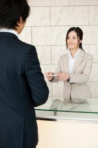 オフィスビルの受付でビジネスマンから名刺を受け取る女性の写真素材 [FYI02069481]