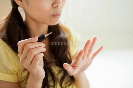 マニキュアを塗っている若い女性の写真素材 [FYI02069484]