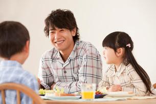 朝食で楽しそうに会話をする父親と子供達の写真素材 [FYI02069490]