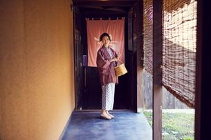 温泉の入り口に立つ浴衣姿のミドル女性の写真素材 [FYI02069494]
