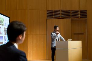 演台で話すミドル男性とビジネスマンの後ろ姿の写真素材 [FYI02069502]