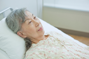 ベッドで横になるシニア女性の写真素材 [FYI02069504]