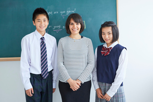 外国人講師と中学生男女のポートレートの写真素材 [FYI02069511]