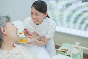 ベッドで横になるシニア女性に食事介助する女性介護士の写真素材 [FYI02069514]