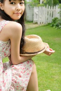 庭先に座りこちらを振り返る若い女性の写真素材 [FYI02069522]