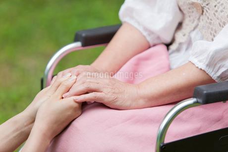 車いすに乗ったシニア女性の手を握る介護士の手元の写真素材 [FYI02069523]