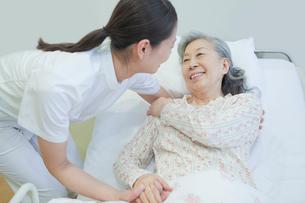 ベッドで横になるシニア女性を介助する女性介護士の写真素材 [FYI02069527]