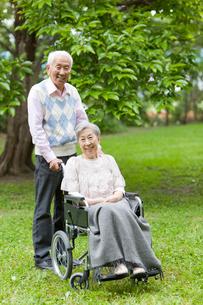 シニア女性の乗った車いすを押すシニア男性の写真素材 [FYI02069528]