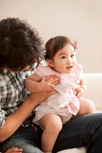 赤ちゃんを膝に抱く若い父親の写真素材 [FYI02069530]