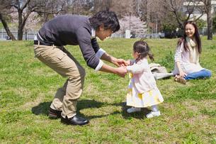 赤ちゃんの手を引き歩かせる父親と見守る母親の写真素材 [FYI02069536]