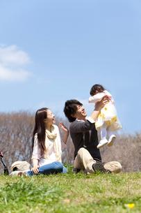赤ちゃんを抱き上げる父親と笑顔で見守る母親の写真素材 [FYI02069544]