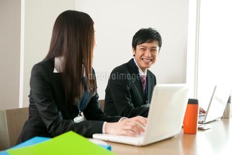 オフィスでノートPCを使い仕事をしている男女の写真素材 [FYI02069562]