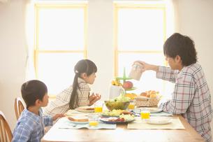 朝食でテーブルに腰掛けて会話をする父親と子供達の写真素材 [FYI02069567]
