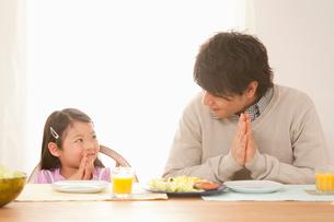 朝食時にいただきますをする娘と若い父親の写真素材 [FYI02069577]