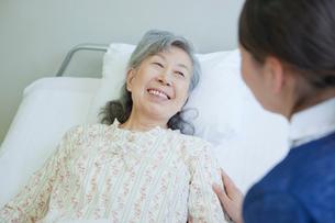 ベッドで看護師と笑顔で会話するシニア女性の写真素材 [FYI02069600]