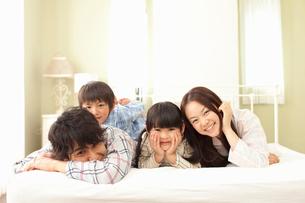 ベッドの上で仲良く微笑むパジャマ姿の4人家族の写真素材 [FYI02069608]