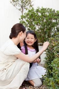庭で寄り添ってしゃがんでいる母親と娘の写真素材 [FYI02069611]