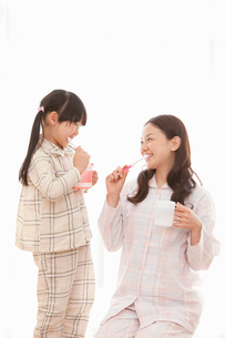 一緒に歯磨きをする娘と若い母親の写真素材 [FYI02069615]