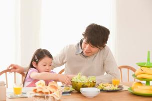 食卓の準備をする娘と父親の写真素材 [FYI02069620]