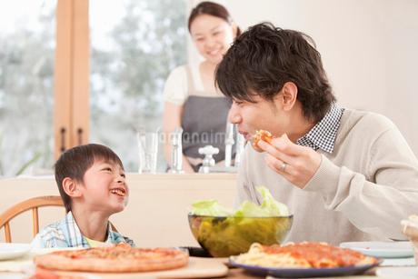 食卓で楽しそうに話す父子と笑顔で見守る母親の写真素材 [FYI02069630]