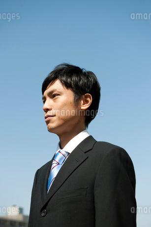 屋外で遠くを見つめるビジネスマンの写真素材 [FYI02069631]