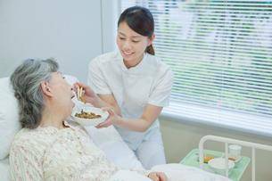 ベッドで横になるシニア女性に食事介助する女性介護士の写真素材 [FYI02069632]