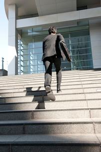 ビルの階段を駆け上がる2人のビジネスマンの写真素材 [FYI02069633]