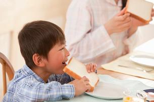 パジャマ姿で朝食をとる母と息子の写真素材 [FYI02069636]