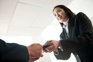 オフィスで名刺交換をするスーツ姿の女性の写真素材 [FYI02069637]