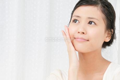 手の平で頬をマッサージする若い女性の写真素材 [FYI02069638]