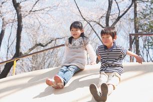 公園の遊具で遊ぶ男の子と女の子の写真素材 [FYI02069642]