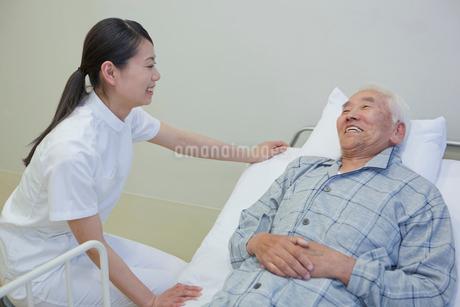 ベッドで横になるシニア男性と笑顔で話す女性介護士の写真素材 [FYI02069645]