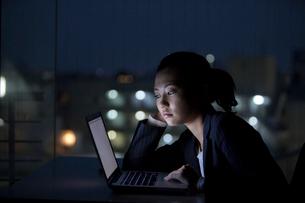 暗闇でノートパソコンを見るスーツ姿の女性の写真素材 [FYI02069646]