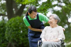 シニア女性の乗った車いすを押す女性介護士の写真素材 [FYI02069647]