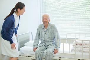 ベッドに座るシニア男性と看護師の写真素材 [FYI02069648]