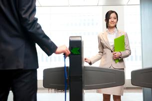 セキュリティのゲートを通るスーツ姿の女性の写真素材 [FYI02069660]