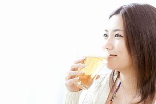 ビールを口に付ける若い女性の写真素材 [FYI02069679]