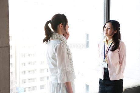 オフィスの窓際で話をする2人の女性の写真素材 [FYI02069684]