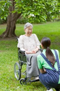 車いすに乗ったシニア女性と話す女性介護士の写真素材 [FYI02069686]